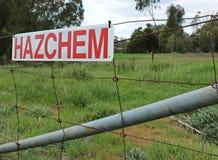 Señal de peligro roja y blanca del hazchem en una cerca de alambre Foto de archivo