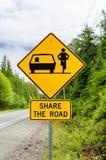 Señal de peligro sobre la bicicleta en el camino Foto de archivo