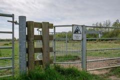 Señal de peligro vista atada a la entrada de la puerta de la granja del metal, que tiene derecho de paso para el público Imagen de archivo libre de regalías