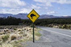 Señal de tráfico amarilla con la travesía del pájaro del kiwi por el camino Montañas en el fondo Localizado en el parque nacional imagenes de archivo