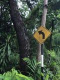 Señal de tráfico amarilla en el jardín Foto de archivo