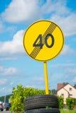 Señal de tráfico amarilla fijada en los neumáticos cerca del camino Imágenes de archivo libres de regalías