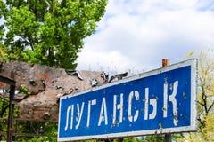Señal de tráfico azul con la inscripción en Lugansk ucraniano, perforado por las balas durante la guerra en el Donbass, conflicto foto de archivo