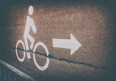 Señal de tráfico blanca de la bicicleta en carril del asfalto con símbolo de la flecha en vin Foto de archivo