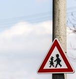 Señal de tráfico con la advertencia - la protección de niños acerca a la escuela Imagen de archivo libre de regalías