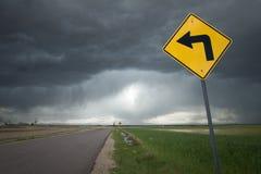 Señal de tráfico con la flecha de la curva de la izquierda y el fondo siniestro de la tormenta Fotografía de archivo