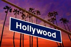 Señal de tráfico de Hollywood California en chino con la foto de los árboles del PAM Imágenes de archivo libres de regalías