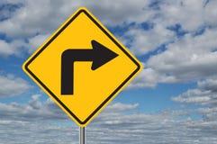 Señal de tráfico de la curva de la izquierda con las nubes Fotos de archivo libres de regalías