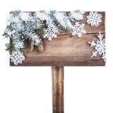 Señal de tráfico de madera con el árbol de navidad en la nieve Fotografía de archivo