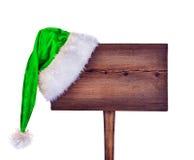 Señal de tráfico de madera con el sombrero de Santa Fotos de archivo libres de regalías