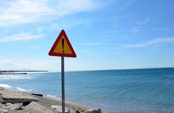 Señal de tráfico del peligro cerca del océano en verano Fotografía de archivo libre de regalías