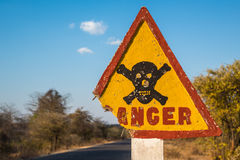 Señal de tráfico del peligro con el cráneo y la bandera pirata Imagen de archivo libre de regalías
