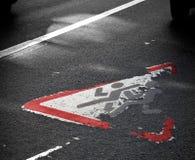 Señal de tráfico en el asfalto con los niños corrientes Foto de archivo libre de regalías