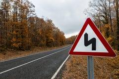 Señal de tráfico en el camino forestal en el otoño fotos de archivo