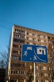 Señal de tráfico europea de vida del sector en Riga, Letonia con un bloque soviético típico de construcción de viviendas de las v imagen de archivo