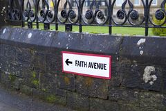 Señal de tráfico de la avenida de la fe que lleva a la iglesia para la adoración religiosa Fotografía de archivo