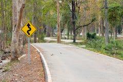 Señal de tráfico de las curvas a continuación Árboles verdes de la naturaleza con BI rural del camino imagenes de archivo