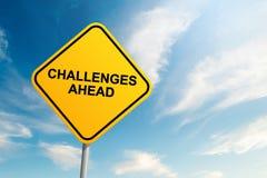 Señal de tráfico de los desafíos a continuación con el fondo del cielo azul y de la nube foto de archivo libre de regalías