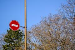 Señal de tráfico ninguna entrada contra el cielo azul y los árboles fotos de archivo