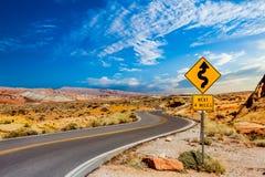 Señal de tráfico para las curvas en desierto imagen de archivo