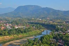 Señal local de Luang Prabang que pasa por alto Nam Khan River y la vecindad local con las montañas en el fondo