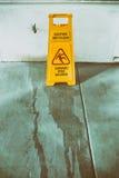Señal y símbolo resbaladizos de peligro de la superficie del piso en el edificio, pasillo Foto de archivo