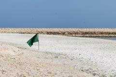Señale la muestra del peligro por medio de una bandera de la natación en el salalah Omán de la bahía de la playa souly Foto de archivo