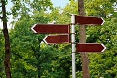 Señales de dirección en blanco de la manera en fondo verde del árbol Imagen de archivo