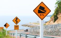 Señales de tráfico de la pendiente escarpada de la colina a lo largo del camino de la playa Imagen de archivo