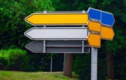 Señales de tráfico direccionales en blanco contra parque flechas del metal en Fotografía de archivo