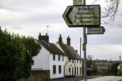 Señales de tráfico de la escuela primaria y de la iglesia en pueblo inglés en Cambridgeshire fotos de archivo