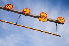 Señales de tráfico rojas y amarillas y alta barra transversal del límite Fotografía de archivo