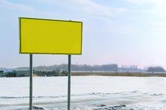 Señalice el soporte en el camino en el invierno, señal de peligro amarilla Imagen de archivo