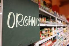 Señalización del alimento biológico en el pasillo moderno del ultramarinos del supermercado fotos de archivo libres de regalías