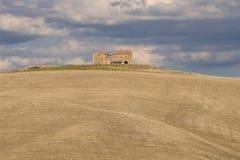 Señorío rural entre campos limpiados debajo de un cielo nublado Otoño en Toscana Foto de archivo libre de regalías