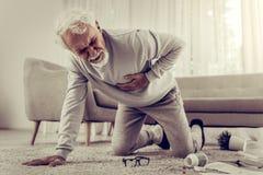 Señor blanco-cabelludo enfermo envejecido del setenta-año que sufre de angustia severa fotografía de archivo