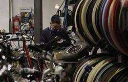 Señor que repara las bicis en su tienda del taller Imagenes de archivo