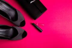 Señora Accessories Set de la moda Negro y color de rosa mínimo Zapatos, lápiz labial y bolso negros en fondo rosado Endecha plana Imágenes de archivo libres de regalías