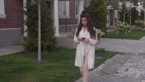 Señora acertada joven que camina abajo de la calle usando su smartphone almacen de video