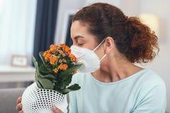 Señora adolescente que prueba su máscara protectora con polen de la flor fotografía de archivo