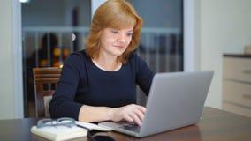 Señora adulta agradable Is Typing Text que usa el ordenador portátil en casa en la tarde almacen de metraje de vídeo