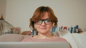 Señora adulta hermosa con el ordenador portátil en un cuarto acogedor La pantalla está reflejando en vidrios almacen de metraje de vídeo
