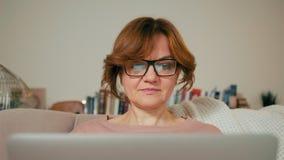 Señora adulta hermosa con el ordenador portátil en un cuarto acogedor La pantalla está reflejando en vidrios Fotografía de archivo libre de regalías