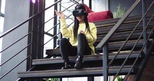 Señora africana apuesta usando los vidrios y disfrutar de la realidad virtual del tiempo usando ellos en un edificio moderno, ell metrajes