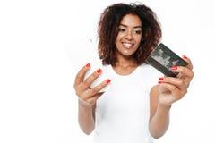 Señora africana joven alegre que usa el teléfono que sostiene la tarjeta de crédito Imágenes de archivo libres de regalías