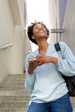 Señora africana joven sonriente que camina abajo de los pasos Imagen de archivo