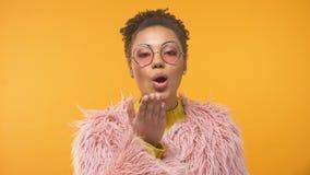 Señora afroamericana de moda en la capa rosada que envía el beso en cámara, encanto del aire almacen de video