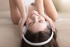 Señora alegre que disfruta de música popular en auriculares Foto de archivo libre de regalías