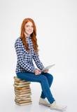 Señora alegre que se sienta en la pila de libros y que usa la tableta Foto de archivo libre de regalías