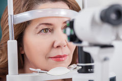 Señora alegre que tiene examen de ojo en oficina del oculista Foto de archivo